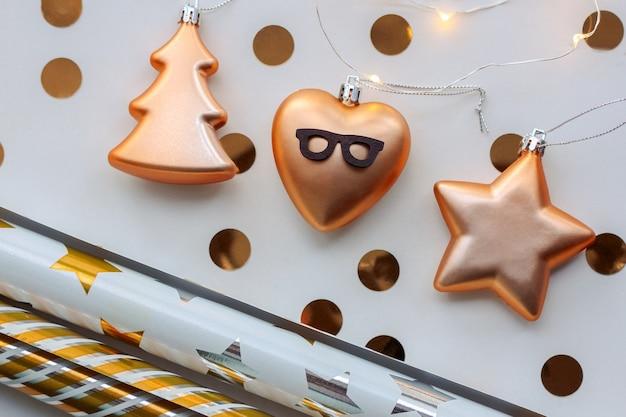 Ornamenti natalizi in oro, stella, albero di natale, cuore con gli occhiali, carta da regalo, coriandoli d'oro, su fondo bianco