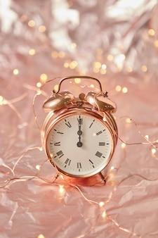 Sveglia dorata di natale su una priorità bassa astratta dorata lucida con lo spazio della copia. l'ora è mezzanotte esatta. biglietto d'auguri.