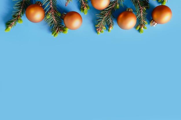 Palle di natale d'oro e rami di abete su sfondo blu