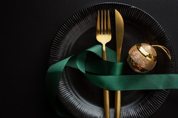 Posate d'oro di natale sul piatto con pallina e nastro sulla superficie scura