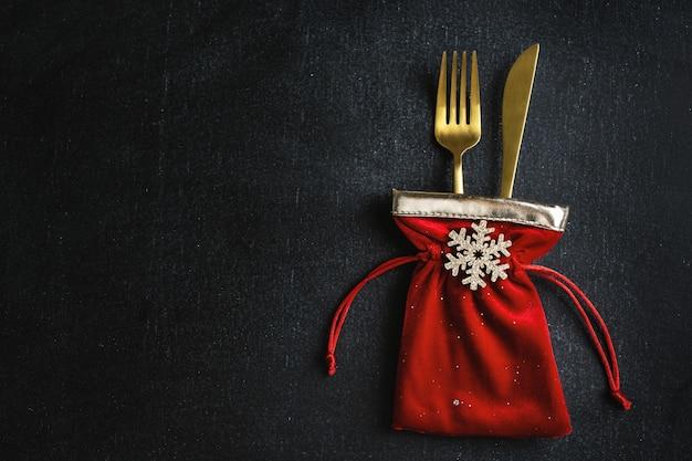 Posate natalizie dorate in piccola borsa in tessuto con fiocco di neve e nastro su fondo nero. lay piatto.