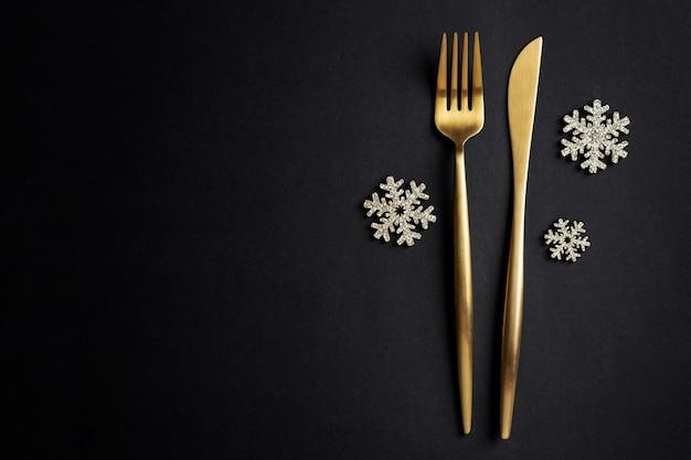 Posate d'oro di natale con fiocco di neve sul nero. lay piatto.