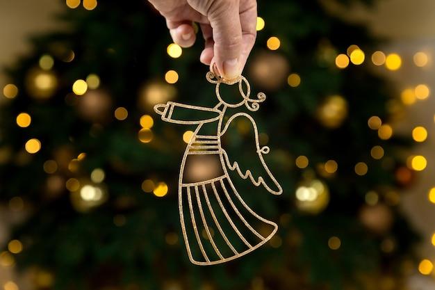 Decorazioni dorate di natale, angelo in mano sull'albero