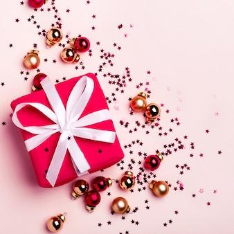 Palle di natale dorate e rosse. confezione regalo rossa su sfondo pastello.