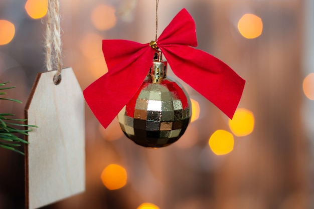 Una palla da discoteca giocattolo d'oro di natale con un fiocco rosso e una forma di legno per un testo di saluto o un design