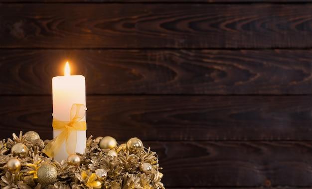 Corona dorata di natale con candela accesa su fondo di legno scuro