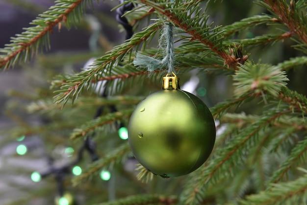 Palla di natale verde appesa all'albero di natale all'esterno.