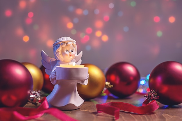 Auguri di natale, candela angelo e palline lucide multicolori.