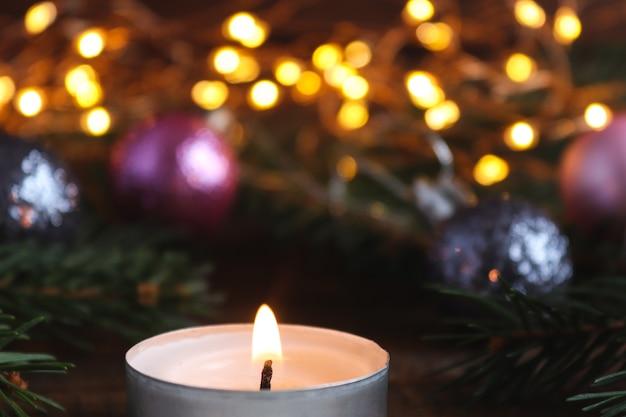Auguri di natale caed con decorazioni natalizie luci rami di albero di natale candela bokeh