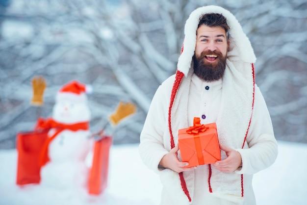 Biglietto di auguri di natale. ritratto di inverno di bei pantaloni a vita bassa nel giardino di neve con regalo fanno pupazzo di neve