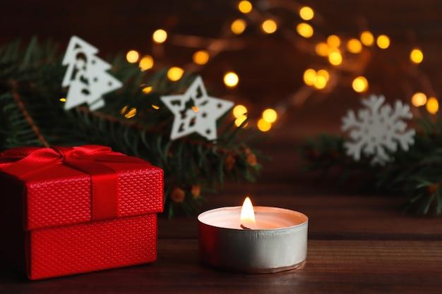 Biglietto di auguri di natale con scatola regalo candela decorazioni natalizie luci rami di albero di natale
