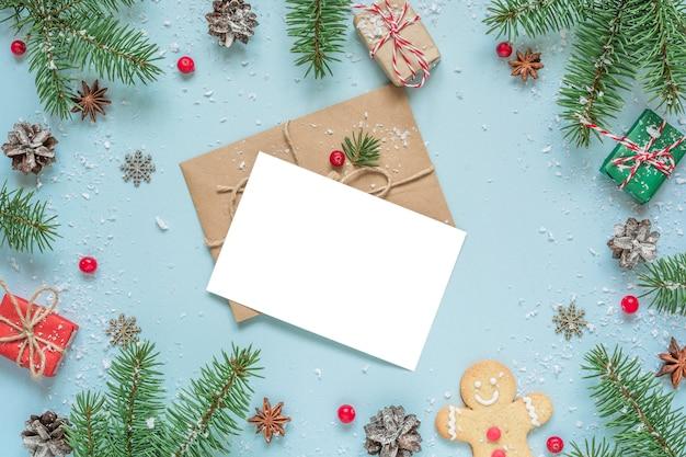 Biglietto di auguri di natale con rami di abete, decorazioni, pan di zenzero su sfondo blu.