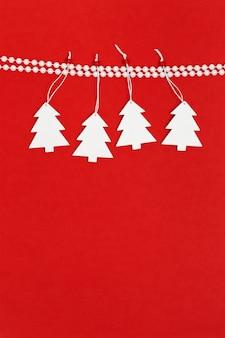 Cartolina d'auguri di natale con l'albero di natale bianco fatto a mano che appende sui branelli della perla della decorazione