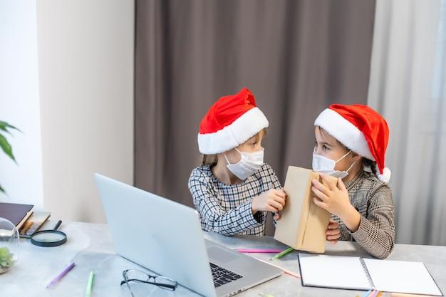 Auguri di natale online. due bambine in mascherine mediche un laptop. mostra regali, acquisti online alla fotocamera.