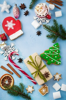 Natale. gruppo di pan di zenzero, cannella, arancia, giocattoli e tazza di cioccolata calda su azzurro.
