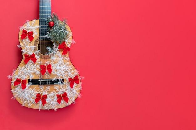 Chitarra di natale su uno sfondo rosso con fiocchi di neve e fiocchi rossi un invito a un nuovo anno