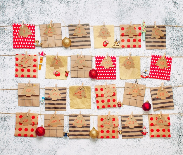 Calendario dell'avvento natalizio fatto a mano di 24 giorni con buste di carta artigianale con palline di natale sul muro