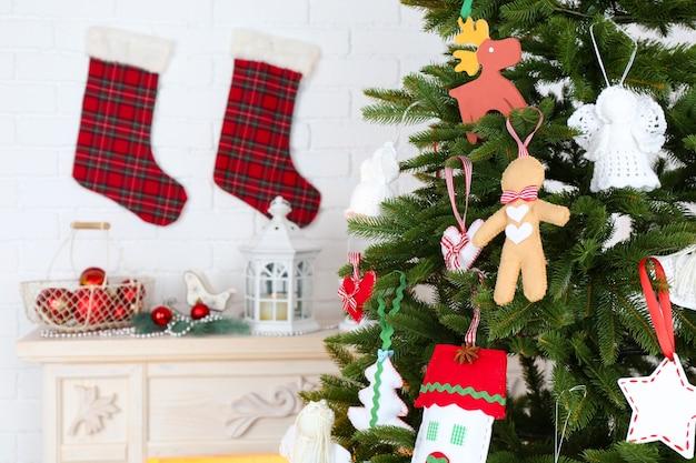 Decorazioni natalizie fatte a mano sull'albero di natale su sfondo chiaro di interni domestici home