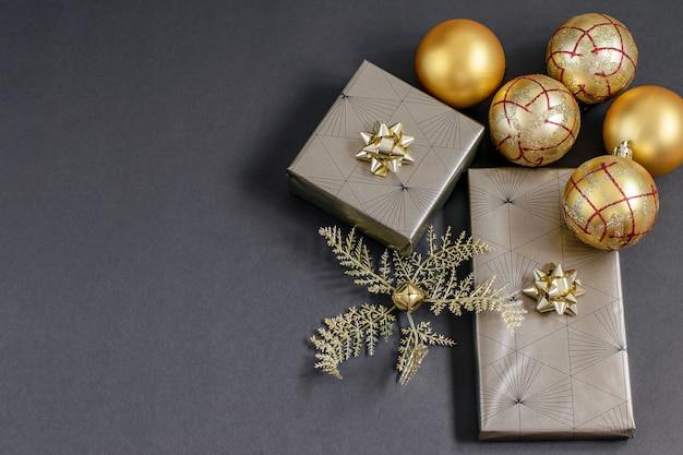 Scatole regalo natalizie fatte a mano incartate e palline e palline color oro fortuna sul nero.