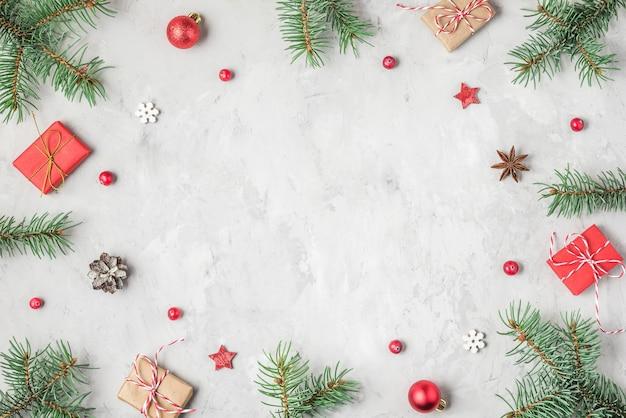 Sfondo di natale o felice anno nuovo fatto di rami di abete, decorazioni natalizie e scatole regalo. laici piatta