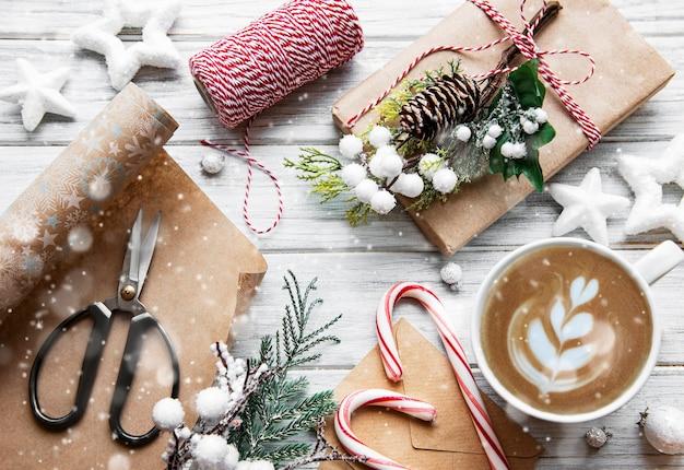 Carta natale e felice anno nuovo con tazza di caffè, pino, abete, scatole regalo su fondo di legno bianco, vista dall'alto