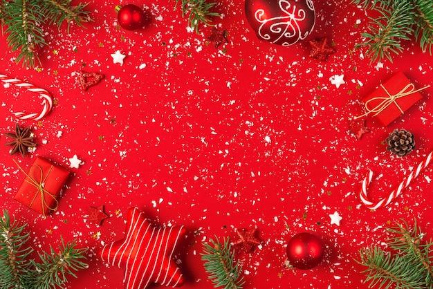 Composizione in natale o felice anno nuovo. cornice fatta di rami di abete, pigne e decorazioni natalizie su sfondo rosso coperto di neve. posa piatta. vista dall'alto con copia spazio