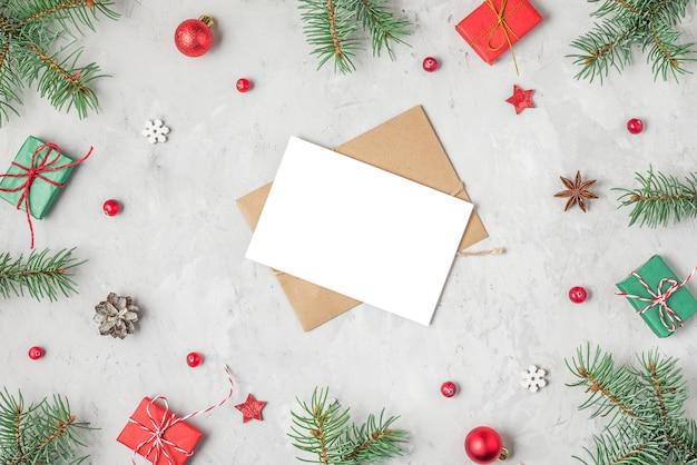 Biglietto di auguri di natale o felice anno nuovo con rami di abete, decorazioni e scatole regalo