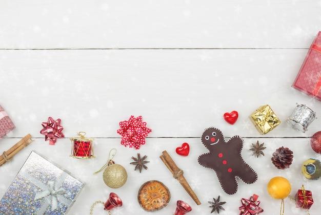 Il piano della decorazione dell'oggetto del buon anno e di natale si trova con lo spazio della copia sul fondo di legno bianco della tavola con le precipitazioni nevose. concetto di congratulazioni e di giri.
