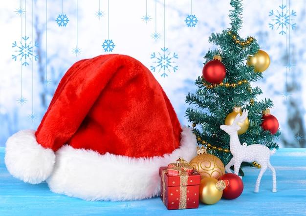 Cappello natalizio con decorazioni natalizie sul tavolo su sfondo chiaro