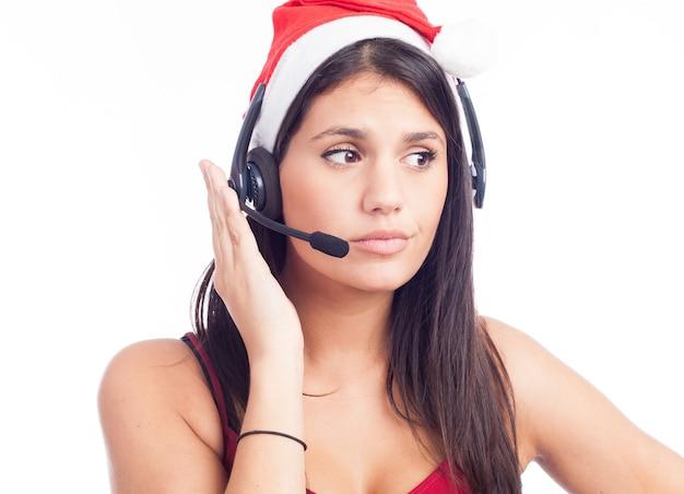 Donna dell'auricolare di natale dal call center di telemarketing che porta la conversazione rossa del cappello della santa