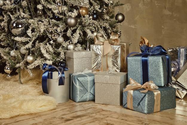 Fondo di festa di natale delle scatole con i regali del nuovo anno sotto l'albero di natale decorato in soggiorno. regali ravvicinati confezionati con nastri, decorazioni sotto l'albero in interni domestici. copia spazio per il sito