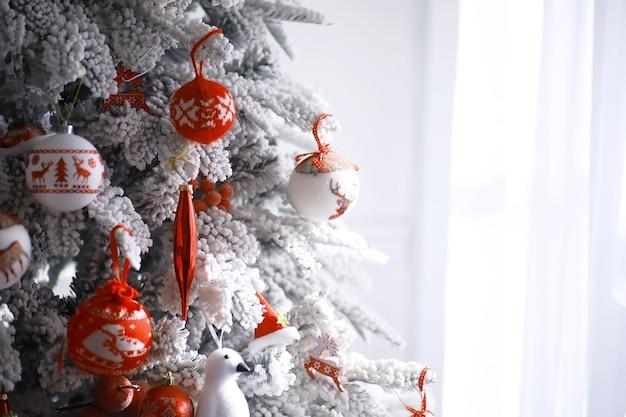 Priorità bassa di festa di natale. pallina d'argento e di colore appesa a un albero decorato con bokeh e neve, spazio copia.