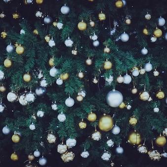 Priorità bassa di festa di natale. pallina d'argento e d'oro appesa a un albero decorato. regalo in confezione dorata lucida sdraiato sul pavimento sotto l'albero. regali di babbo natale.