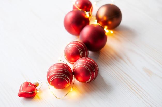 Fondo di festa di natale con le palle e la ghirlanda rosse di natale