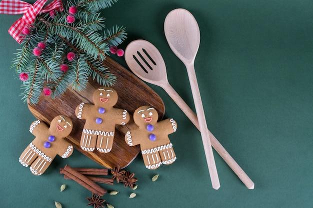 Cottura natalizia e festiva. biscotti degli uomini dello zenzero con la decorazione su superficie verde