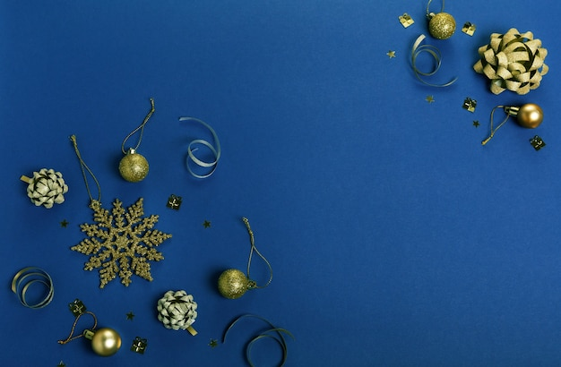 Composizione per le vacanze di natale. reticolo creativo festivo dell'argento dell'oro, sfera di festa dell'arredamento di natale con il nastro, fiocchi di neve su fondo blu classico. colore dell'anno 2020 blu classico. disposizione piatta, vista dall'alto
