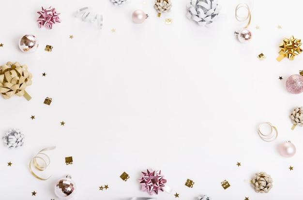 Composizione per le vacanze di natale. reticolo creativo festivo dell'argento dell'oro, palla di festa dell'arredamento rosa di natale con il nastro, fiocchi di neve su fondo bianco. disposizione piatta, vista dall'alto