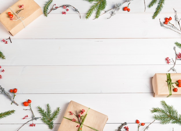Composizione per le vacanze di natale. modello creativo festivo, decorazioni natalizie con regali di festa, rosa canina decorata di bacche, nastro, fiocchi di neve, albero di natale su fondo di legno bianco. disposizione piatta, vista dall'alto