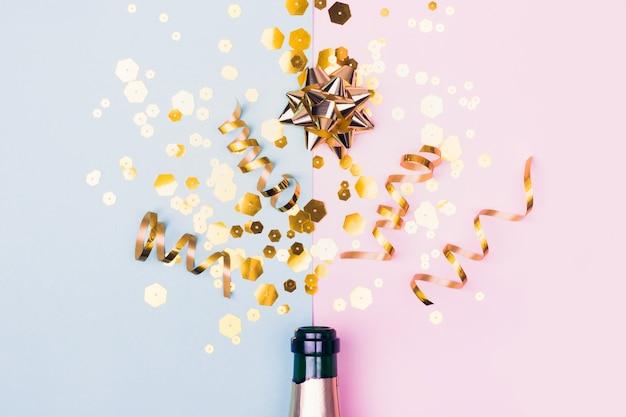 Composizione per le vacanze di natale con scintillii dorati di bottiglia di champagne su sfondo rosa blu. concetto creativo del partito.