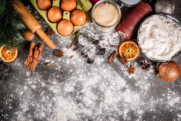 Natale, cucina festiva. ingredienti, spezie, arance essiccate e stampi da forno, decorazioni natalizie (palline, ramo di abete, coni), sul tavolo di pietra nera, vista dall'alto