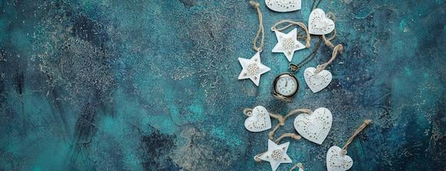Cornice per le vacanze di natale con decorazioni festive - cuori in metallo bianco e vecchi orologi pjcket sul vecchio blu. natale con copia spazio