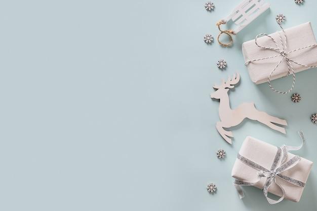 Cornice per le vacanze di natale con regali, decorazioni in legno bianco, cervi e fiocchi di neve