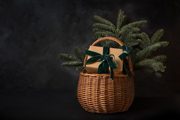 Cesto regalo per le vacanze di natale con regalo artigianale e rami di spezie sempreverdi su uno spazio nero