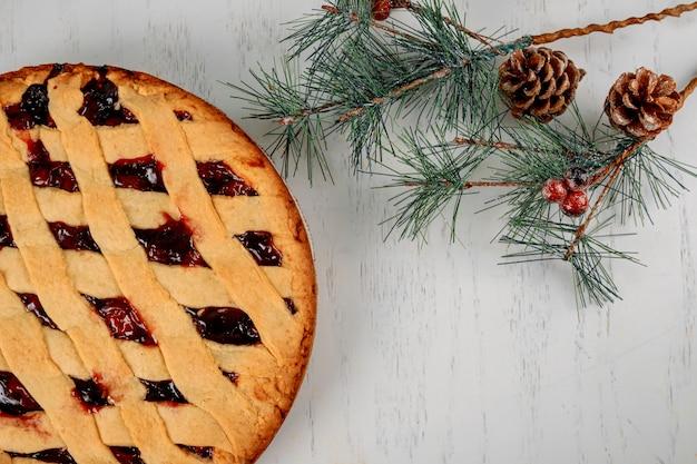 Festa di natale con la torta di mele e l'albero di abete sulla tavola di legno con la disposizione del piano di vista superiore dello spazio della copia