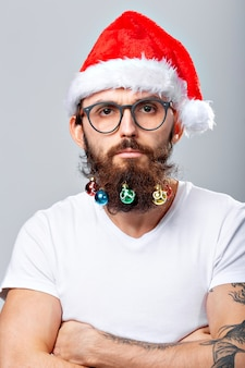 Natale, vacanze, barbiere e concetto di stile - giovane e bello barbuto babbo natale con tante piccole palline di natale in barba lunga.