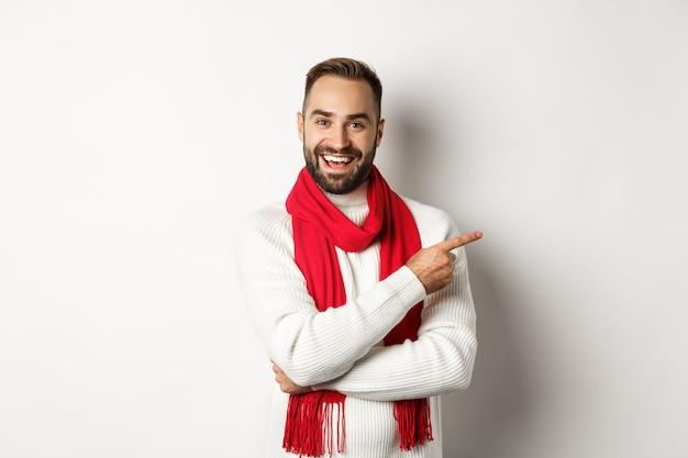 Vacanze di natale e concetto di celebrazione. felice uomo barbuto che punta il dito proprio nello spazio della copia, mostrando l'offerta pubblicitaria, in piedi su sfondo bianco