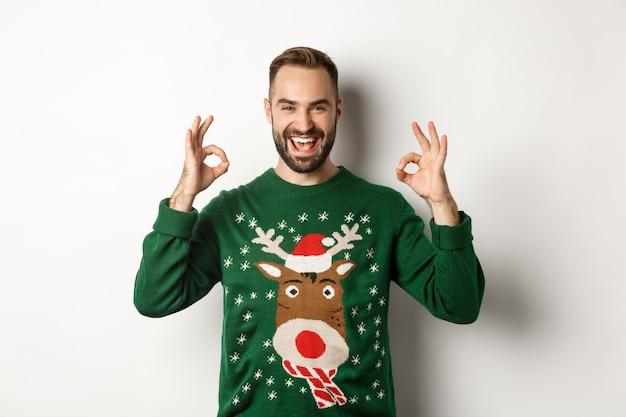 Natale, feste e celebrazioni. un bel ragazzo soddisfatto in maglione, che mostra segni ok e sorride, loda qualcosa di grande, in piedi su sfondo bianco