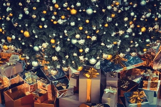 Natale, vacanze, regali, capodanno e concetto di celebrazione - chiusura di scatole regalo sotto l'albero di natale su pavimento di legno.