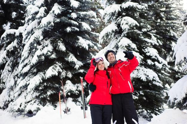 Vacanze di natale nella foresta invernale. il ritratto degli amanti con gli sci gode dell'inverno nel parco.