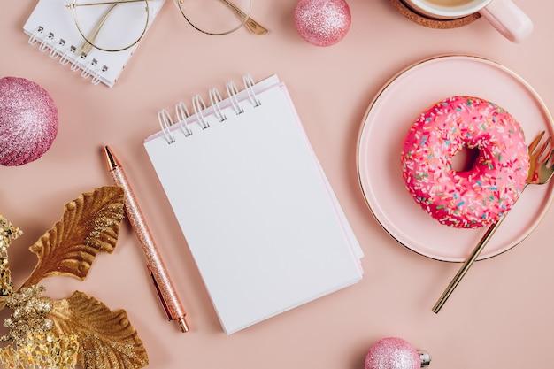 Scrivania da ufficio natalizia con tastiera del computer, ciambella, tazza di caffè e decorazioni natalizie
